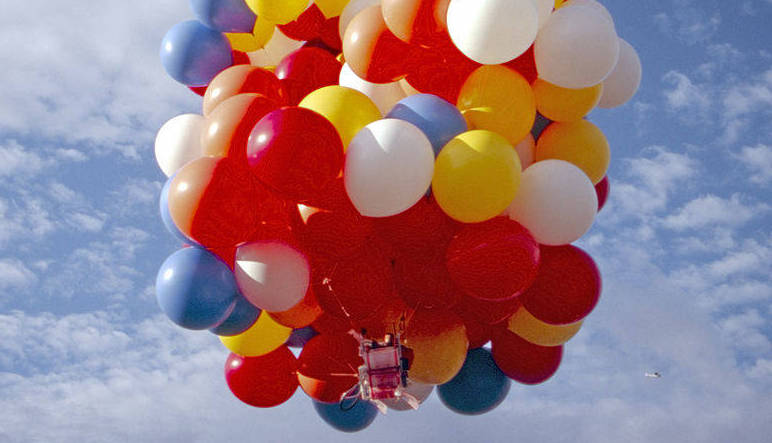 Man floating in a Lawnchair thanks to helium balloons